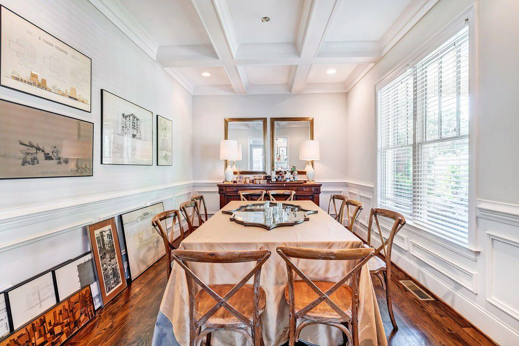 A white dining room with a  long dining table and bar.