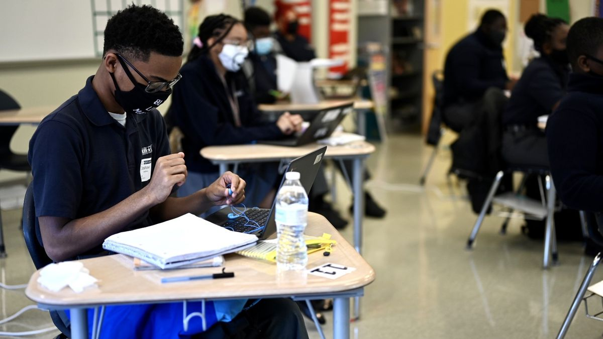 A young man works at his desk, wearing glasses, a protective mask, and a blue polo shirt. Several other students work at their desks around him in a classroom.
