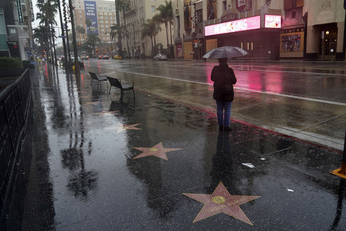 A woman waits at a bus stop in the rain Monday, Dec. 28, 2020, in the Hollywood section of Los Angeles. Rain, hail and snow fell Monday as Southern California saw its first significant storm of the season.