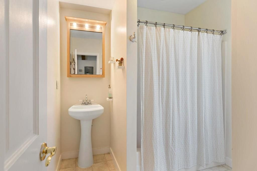 A bathroom facing the sink and next to it is a shower with a curtain pulled shut.