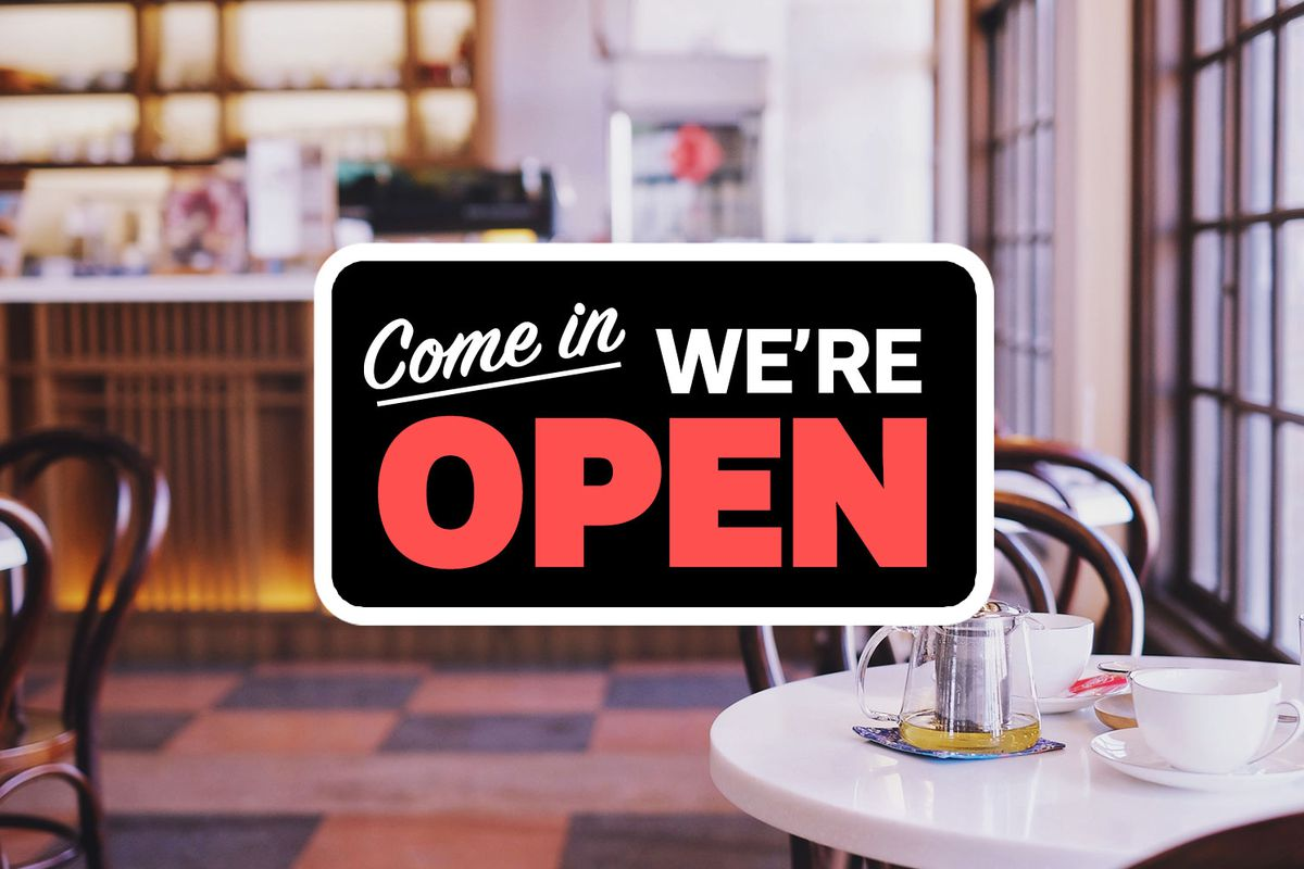 A Come On We're Open sign in front of a photo of a restaurant with a counter, tiled floors, and a table with a tea pot