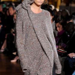 """Cara wore this enormous shoulder knotted sweater dress, continuing the trend of crazy huge knits we first saw from <a href=""""http://racked.com/archives/2014/02/11/olsens-will-have-you-swimming-in-your-clothing.php"""">The Row</a> in New York."""