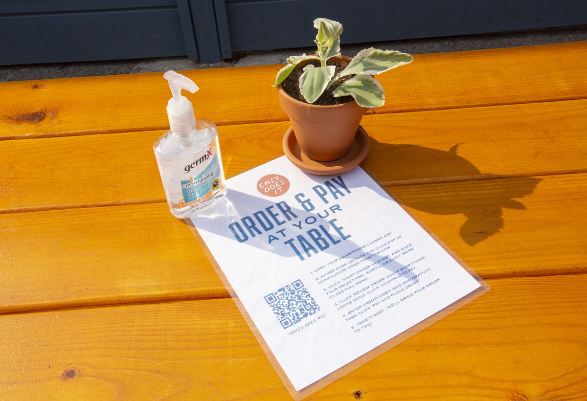 A laminated menu, a pump bottle of hand sanitizer, and a potted pant on a wooden table.
