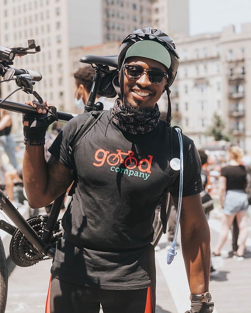 A man wearing a helmet and sunglasses smiling while carrying a bike