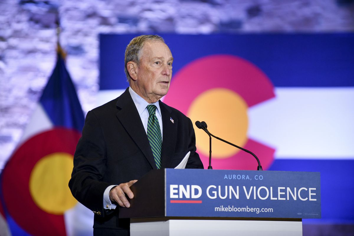 "Presidential candidate Mike Bloomberg speaking at a podium that read, ""End gun violence."""