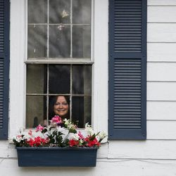 Regina Williams looks out the window of her freshly painted home in Glouster, Ohio on April 16, 2012. Building by building,  volunteers are trying to perk up their Athens County village of 2,000, hoping that a little cosmetic work can boost the community's spirit.