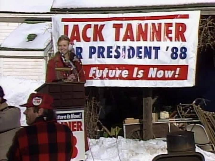 """A college-aged woman stands in front of a poster that reads """"Jack Tanner for President '08. The future is now!"""""""