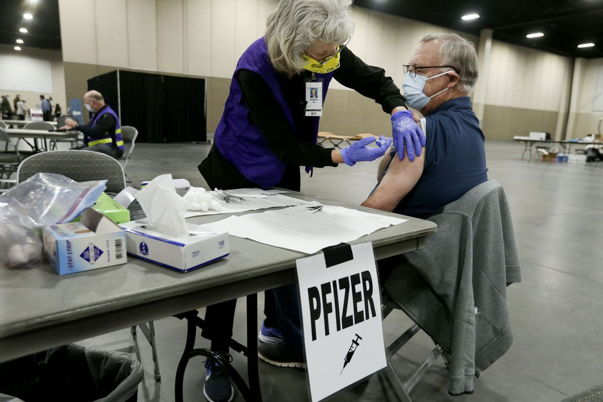 Andrea Culp, left, gives George Conover, of Sandy, a COVID-19 vaccination at the Mountain America Exposition Center in Sandy on Thursday, Feb. 11, 2021.