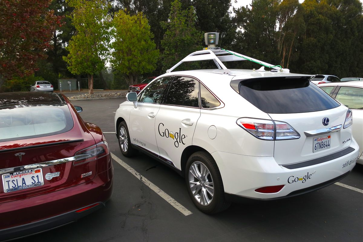 A Mercedes outfitted by Google with a self-driving system, parked next to a Tesla in a public parking lot.