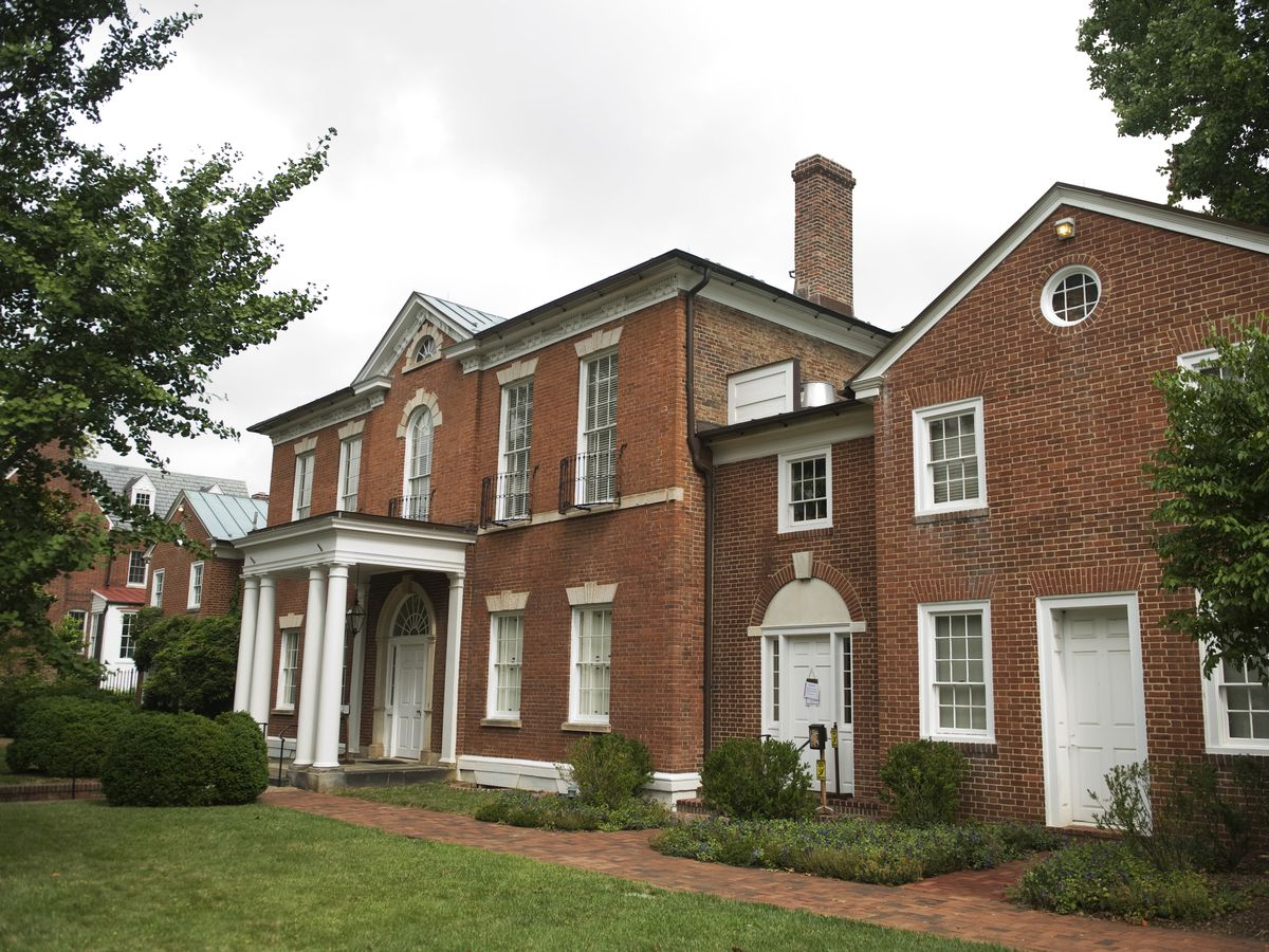 The exterior of the Dumbarton House. The facade is red brick with white columns and a chimney.
