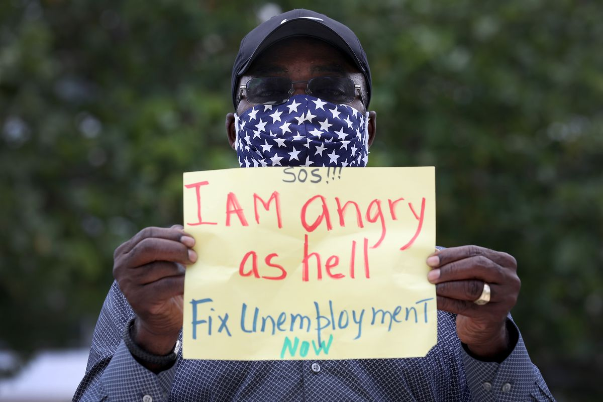 "The man, in a blue mask with white stars, holds a sign written on a yellow piece of paper. It reads: ""SOS!!! I AM angry as hell Fix Unemployment NOW."""