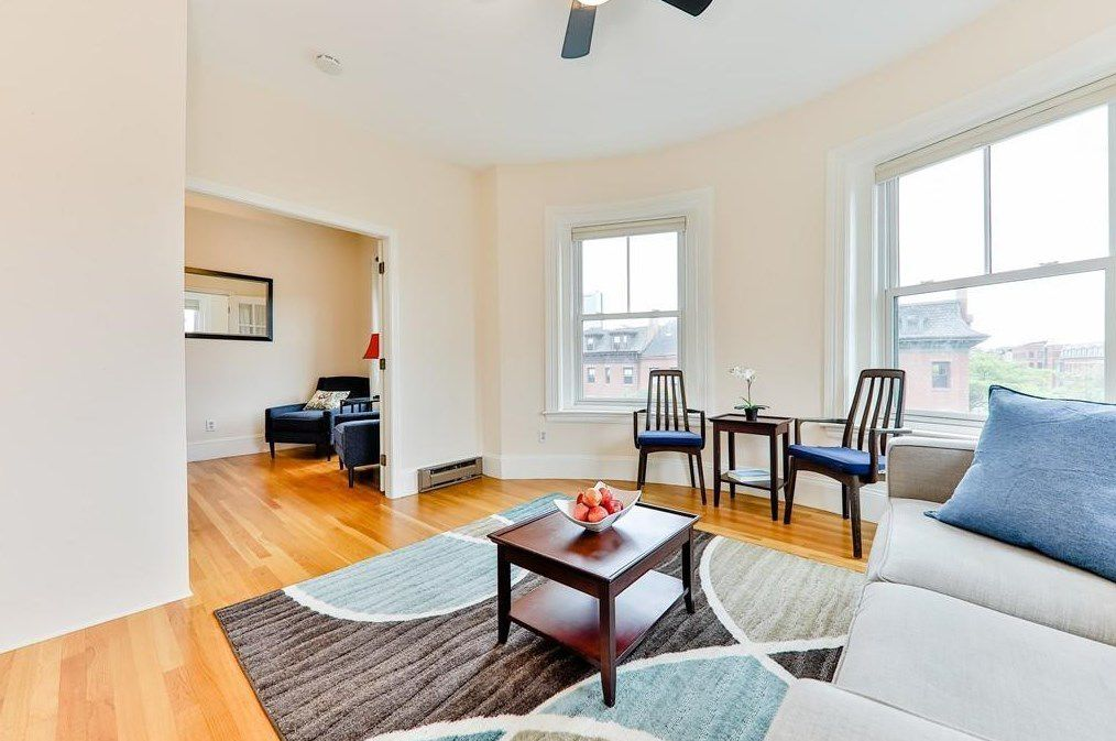 A larger room next to the living room with a couch, and both rooms have larger windows.