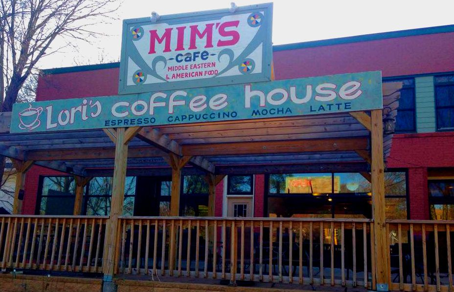 The exterior of Mim's Cafe, a maroon building with a large, hand painted sign touting Mim's Cafe, and Lori's Coffee House