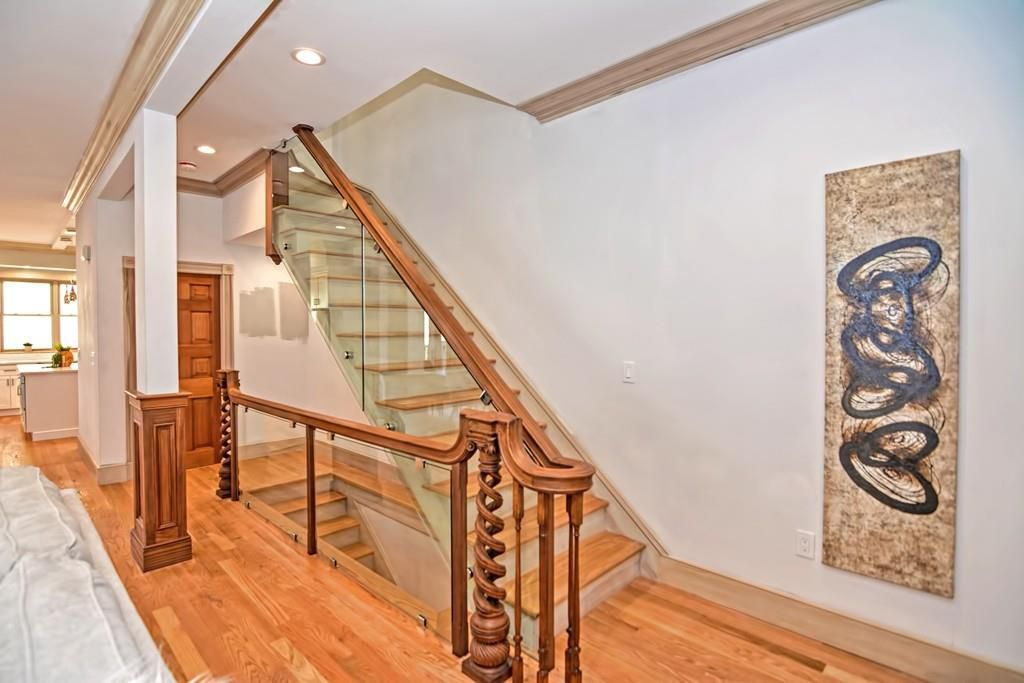 The landing of a staircase, the banister of which is made partially from glass.