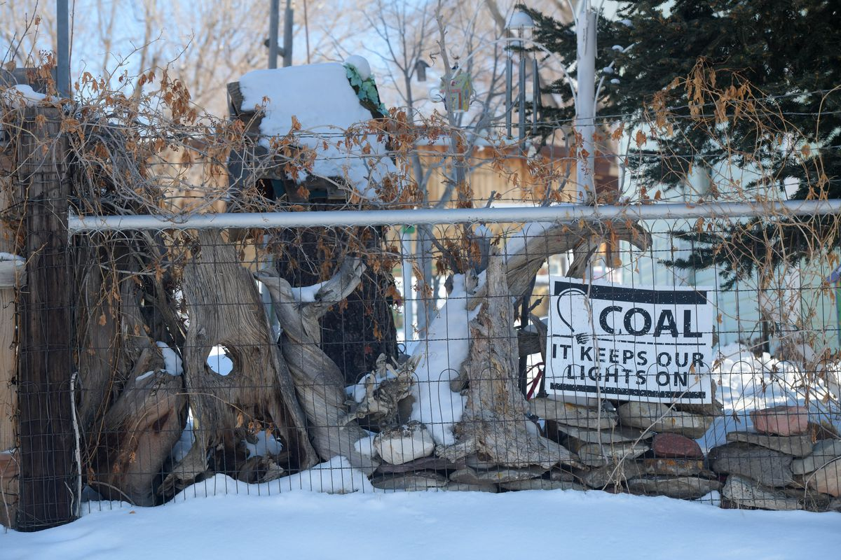 A sign tied to a fence that reads: Coal, it keeps our lights on.