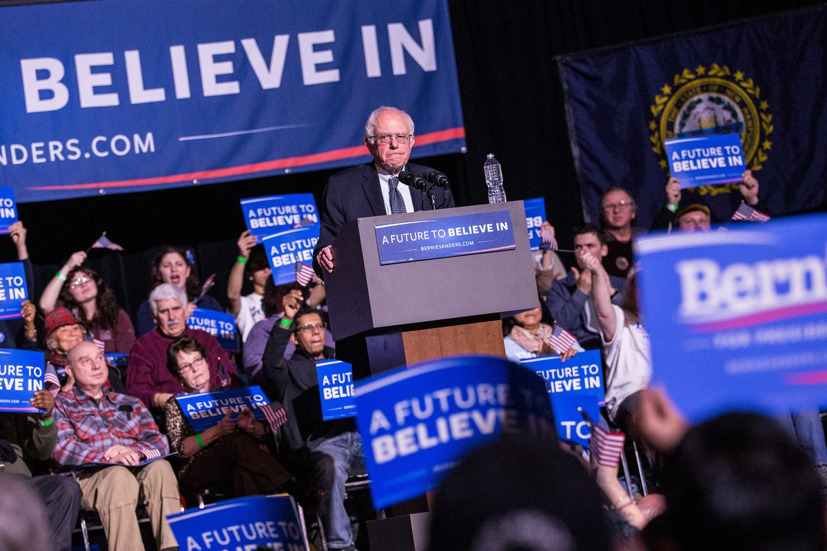 """Bernie Sanders standing behind a podium at a 2016 campaign rally where signs read, """"A future to believe in."""""""