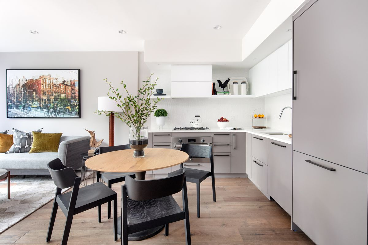 A kitchen with a round table and white and grey cabinetry.