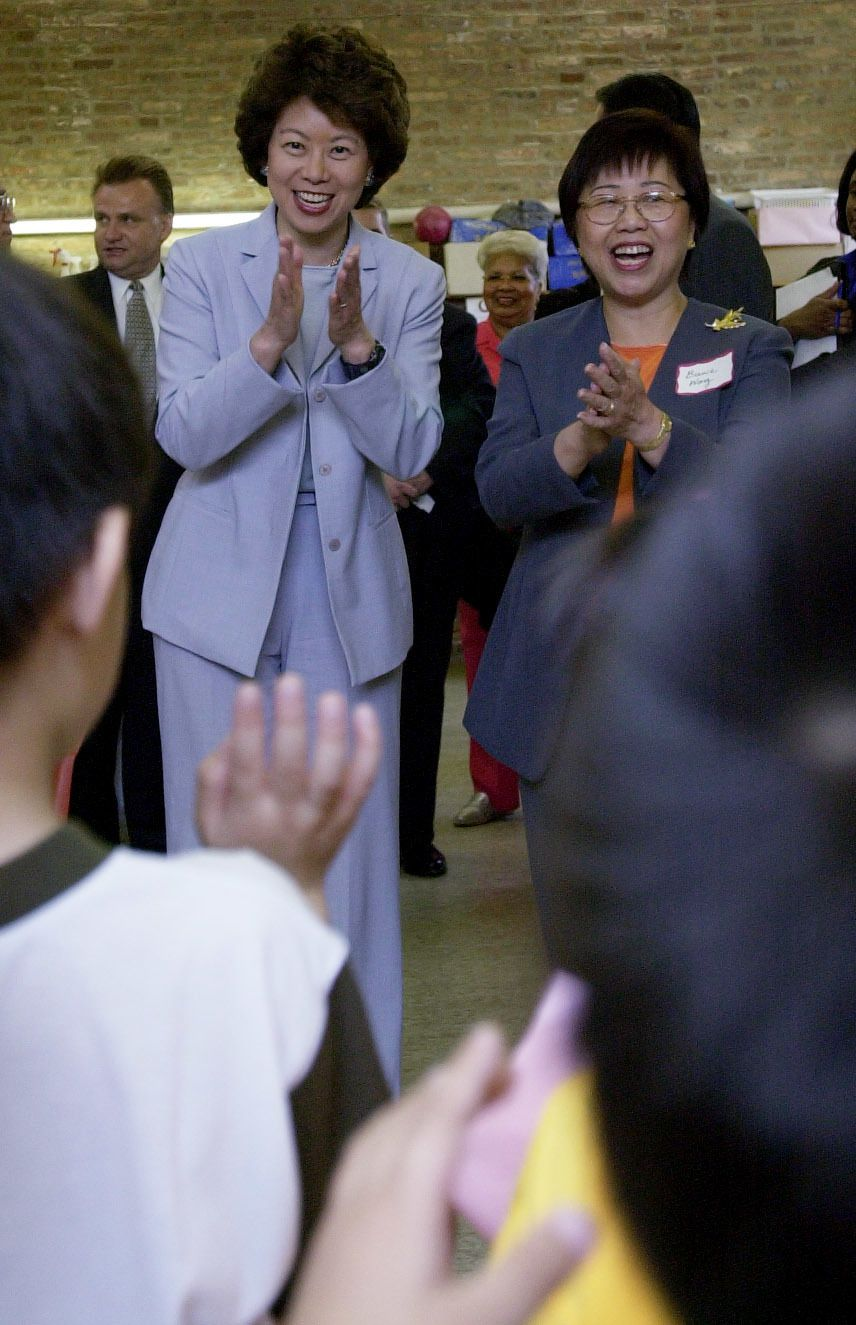 Then U.S. Labor Secretary Elaine L. Chao, left, and Bernie Wong, president of the Chinese American Service League, clap along as children in the center's day care sing a welcome song to the secretary, who toured the facility in 2001.