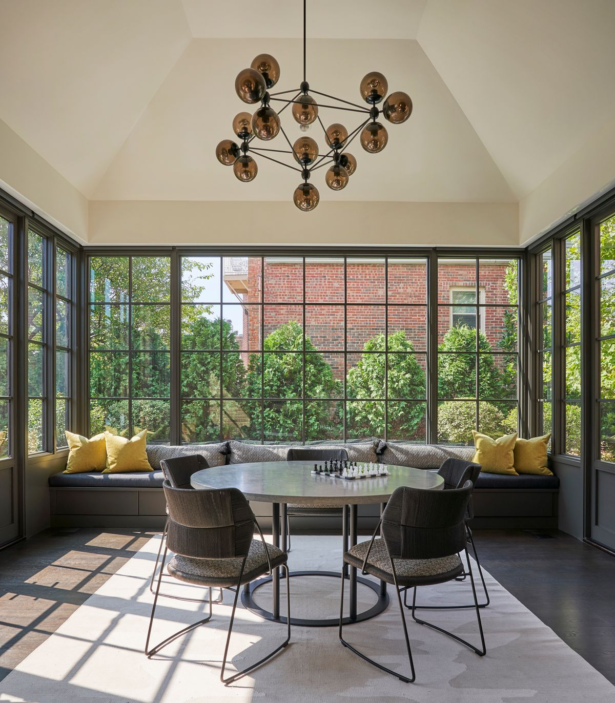 Sunroom with benching seat and a table to play games at.