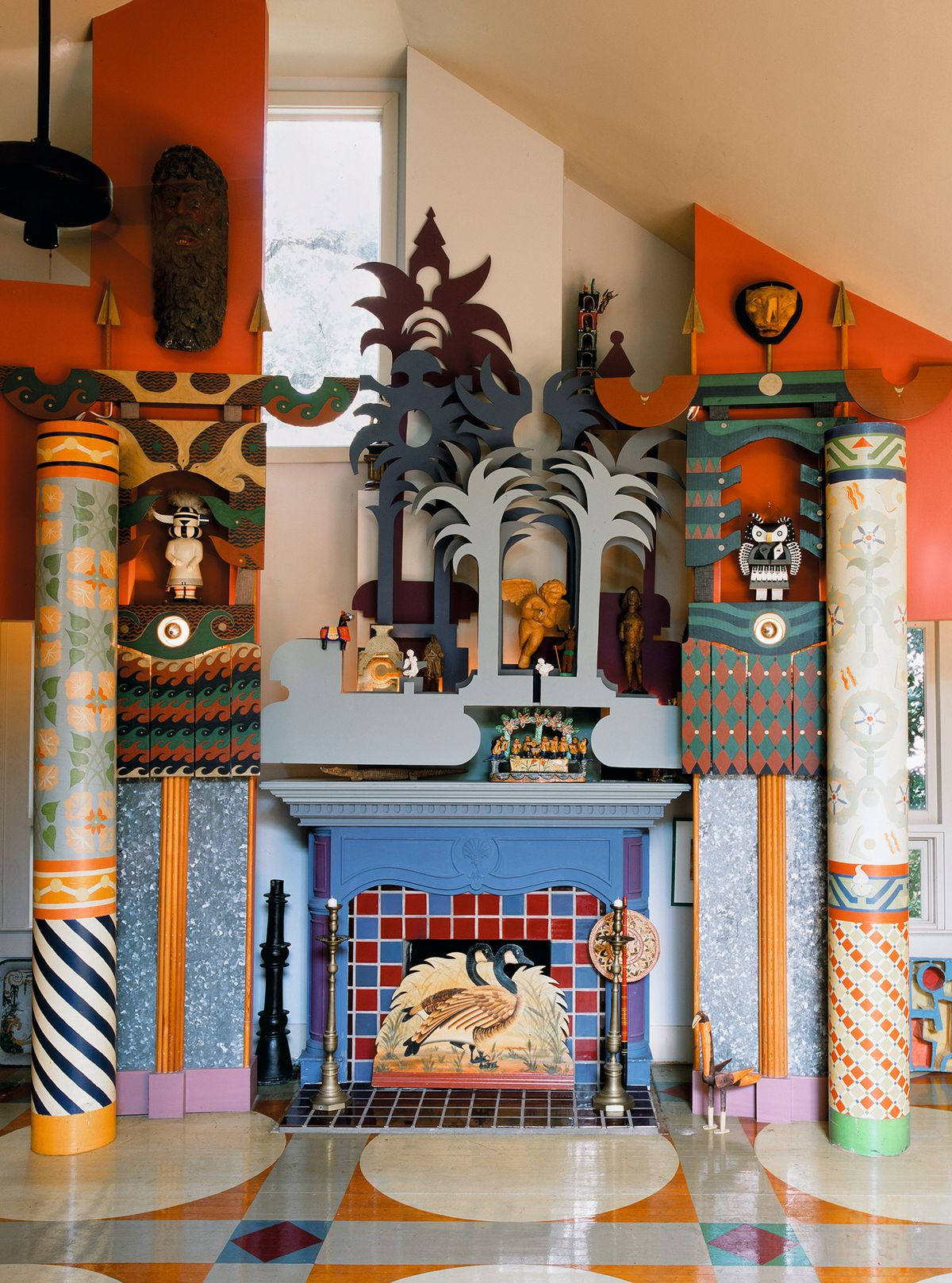 A blue mantle surrounded by blue palm trees, kachinas, masks, and colorful tile. The walls are painted orange and the floor is polychromatic.