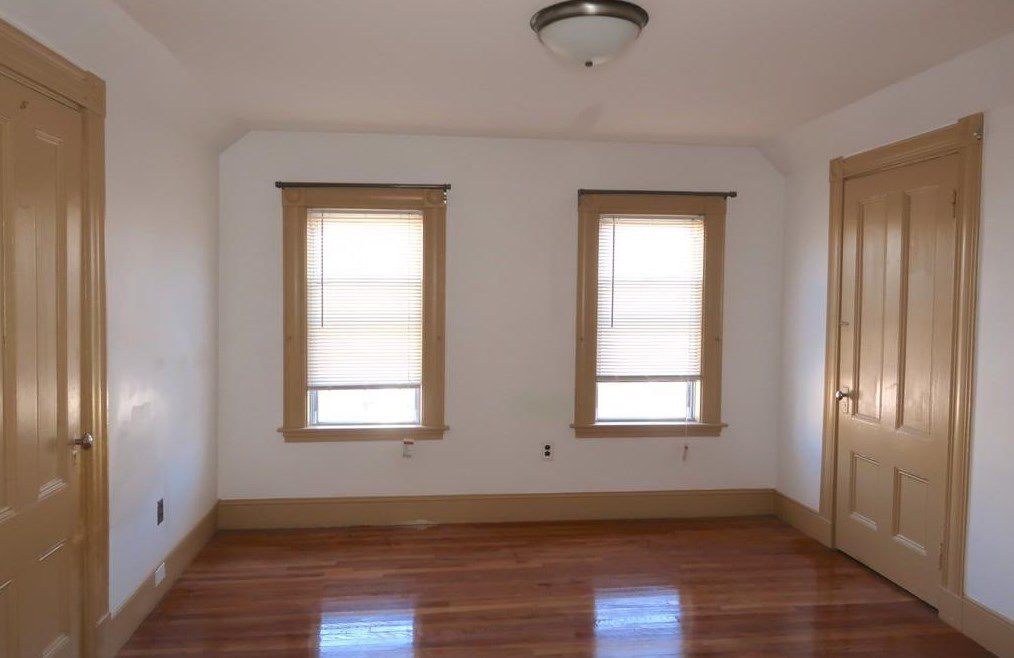 An empty room with two windows and two closed closet doors.