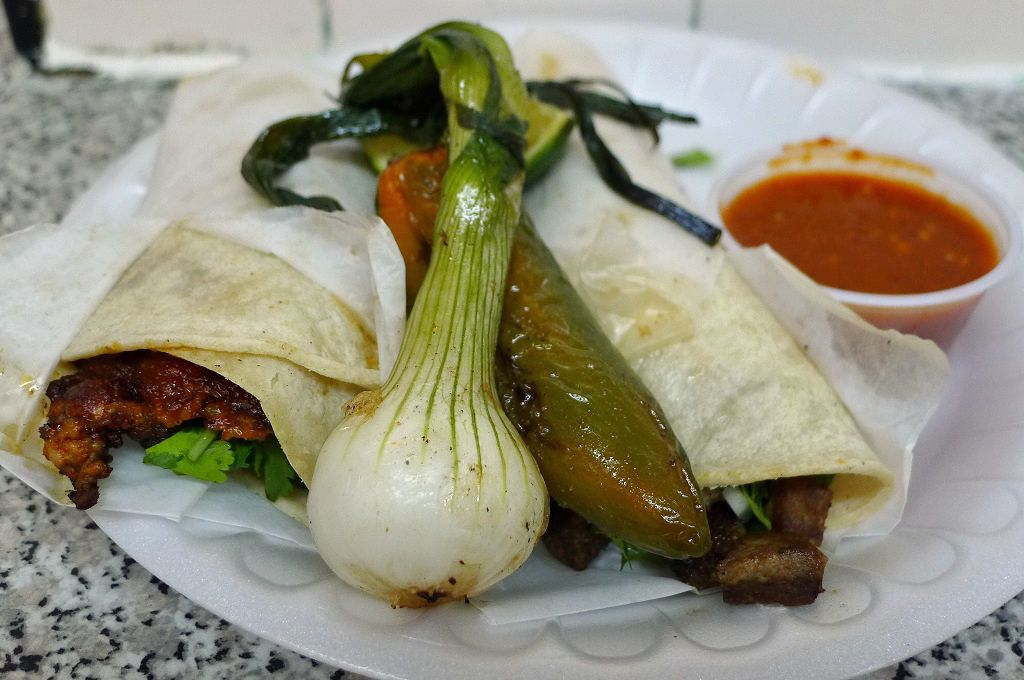 A pair of rolled tacos with bulbous white onion with green shoots and glistening jalapeno.