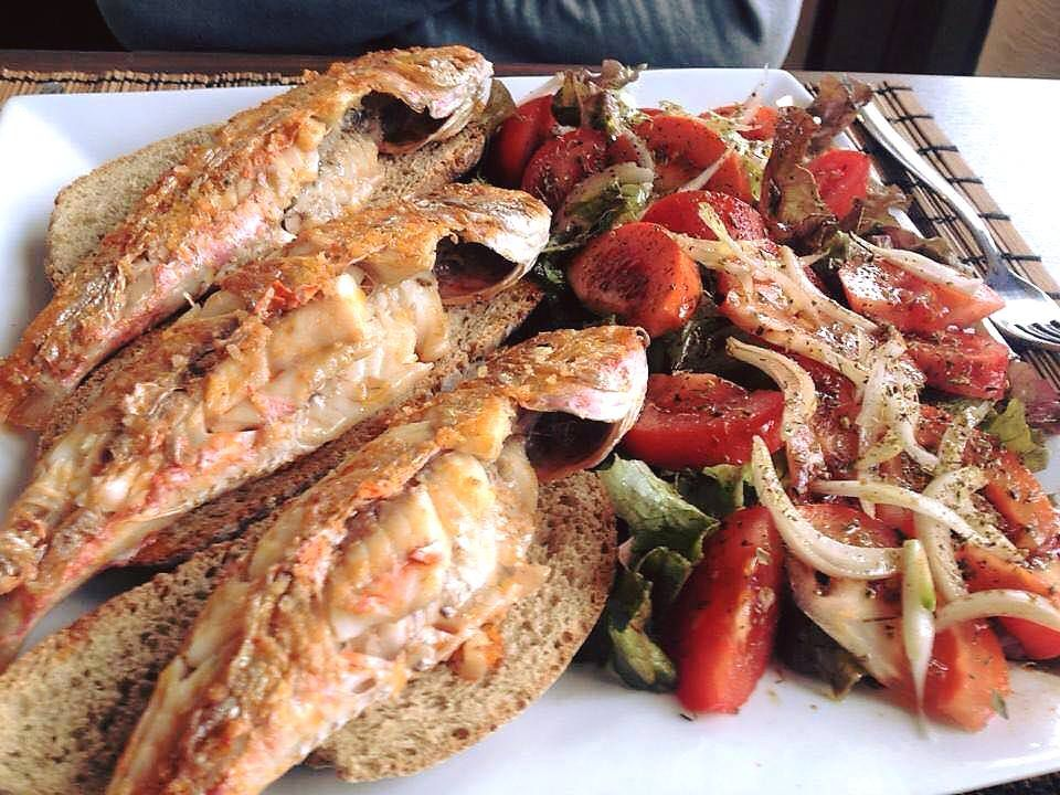 Three whole fried fishes sit on slices of bread on the left side of a plate beside a salad of onions and tomatoes