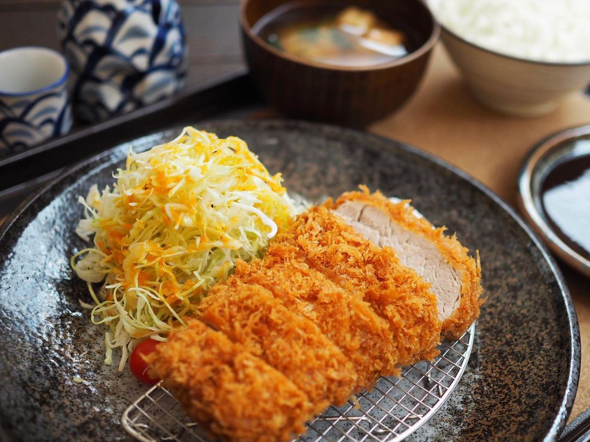 Tonkatsu cutlet next to mound of shredded cabbage.
