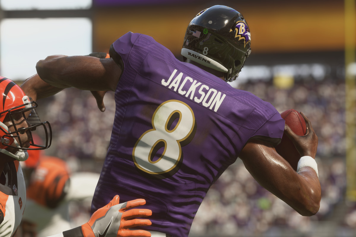 Seen from behind, Ravens quarterback Lamar Jackson tries to throw the ball as a Cincinnati Bengals defensive back closes in for a sack.