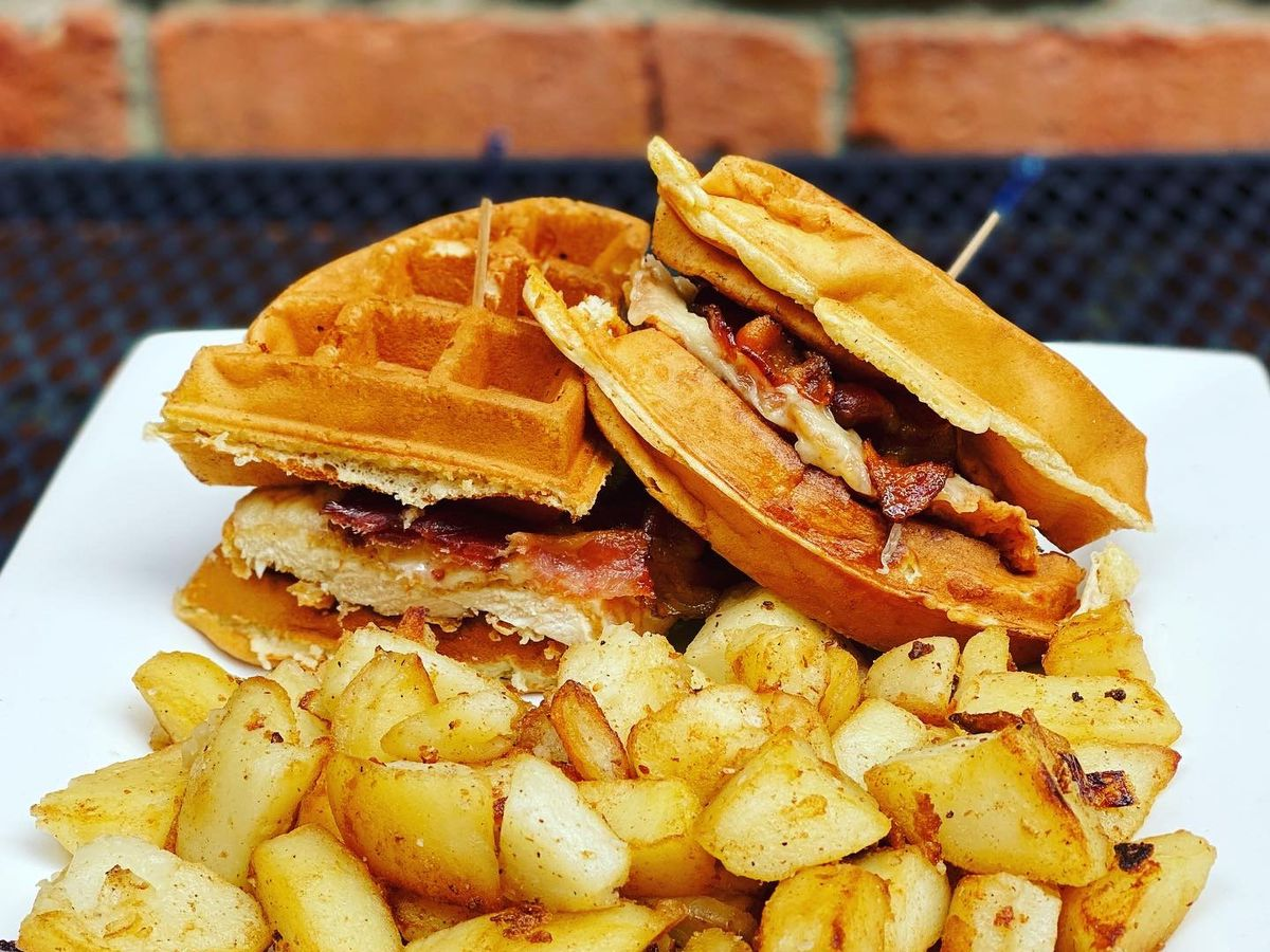Closeup photo of a fried chicken sandwich where the bread is made of waffle. The plate is filled with home fries, too. A brick wall is visible in the background.