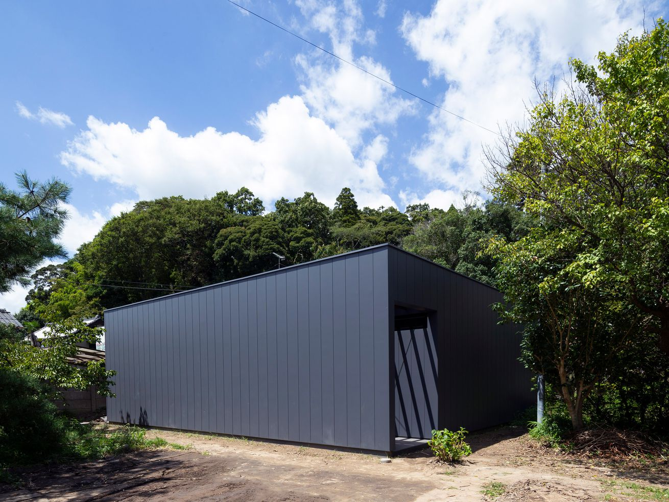 A black-colored boxy house is surrounded by trees.