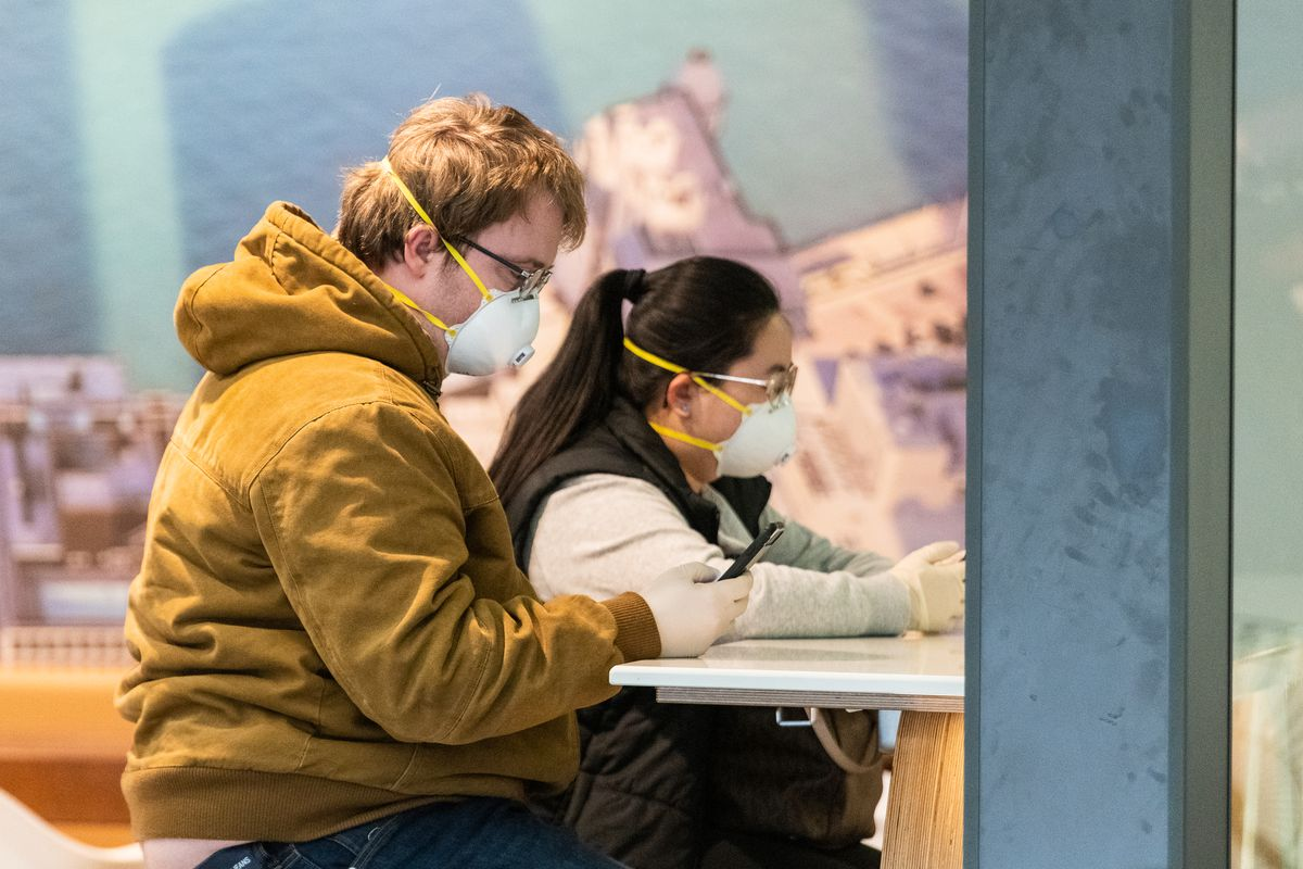 A couple wears face masks and latex gloves Friday in the international terminal at O'Hare Airport.