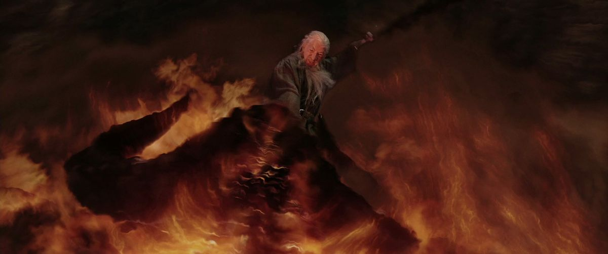 Gandalf raises his sword to strike as he rides the falling Balrog down their endless fall in The Lord of the Rings: The Two Towers.