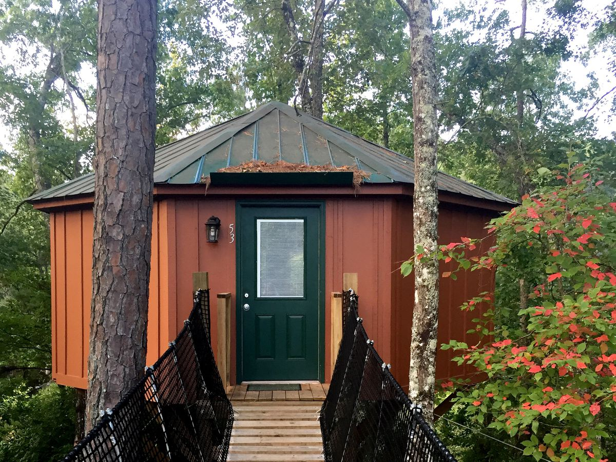 A treehouse with a bridge leading to the entrance. The treehouse is orange with a brown roof.