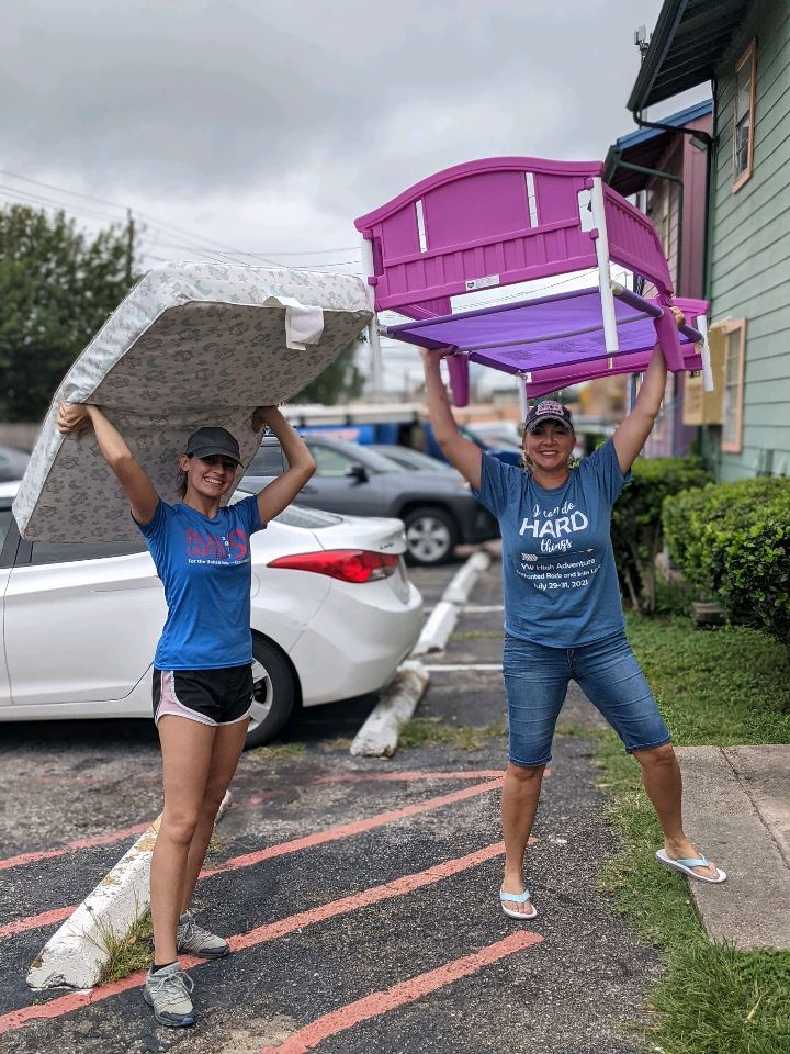 Volunteers carry a bed frame and mattress as part of a service project to furnish apartments for incoming refugee families in Houston.