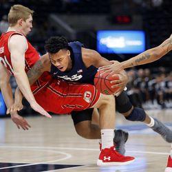 Utah State Aggies forward Dwayne Brown Jr. is called for a charge against Utah Utes forward Tyler Rawson during NCAA basketball at Vivint Smart Home Arena in Salt Lake City on Saturday, Dec. 9, 2017.