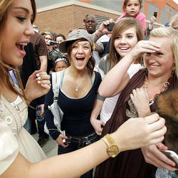 """Miley Cyrus greets fans, from left, Taylor Evangelista, Chantel Mundy, Katelyn Neilson and Alexis Kener, at the Megaplex 20 in South Jordan, on Friday, prior to the premiere of her movie, """"Hannah Montana."""" Cyrus named the dog being held by Kener, who hadn't chosen a name for the shih tzu. Cyrus named him Rascal."""
