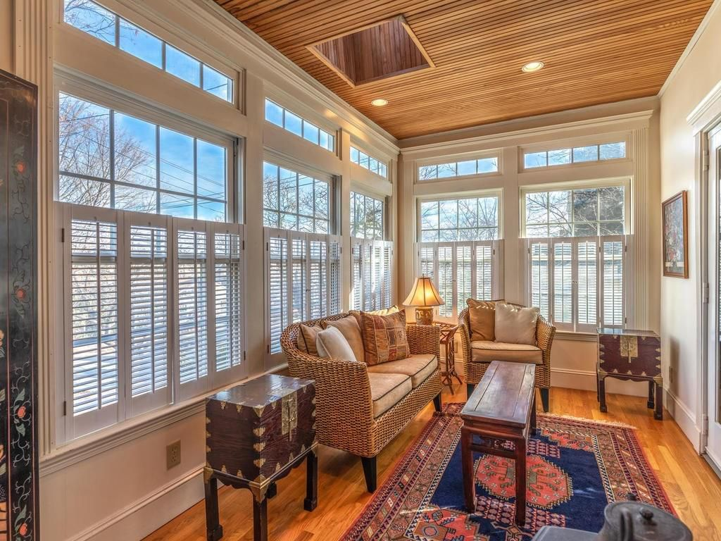 A sunroom with furniture and windows with shutters.
