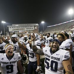 Utah State players sing the school's song while celebrating with fans after winning 26-23 against Washington State in an NCAA college football game, Saturday, Sept. 4, 2021, in Pullman, Wash.
