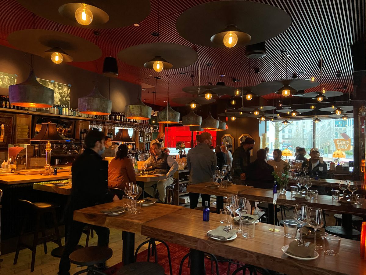 about 15 people dining at tables scattered throughout a dimly lit Storico Vino in Buckhead Atlanta. A man in dark jacket, dark pants, and a baseball cap wearing a blue surgical mask walks between two high top tables