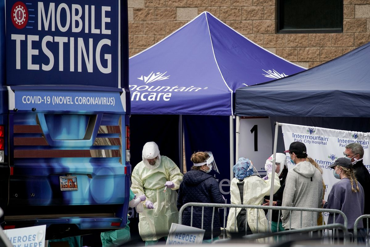 Health care workers test people for COVID-19 at Intermountain Healthcare's mobile testing unit at Park City High School on Saturday, April 18, 2020.