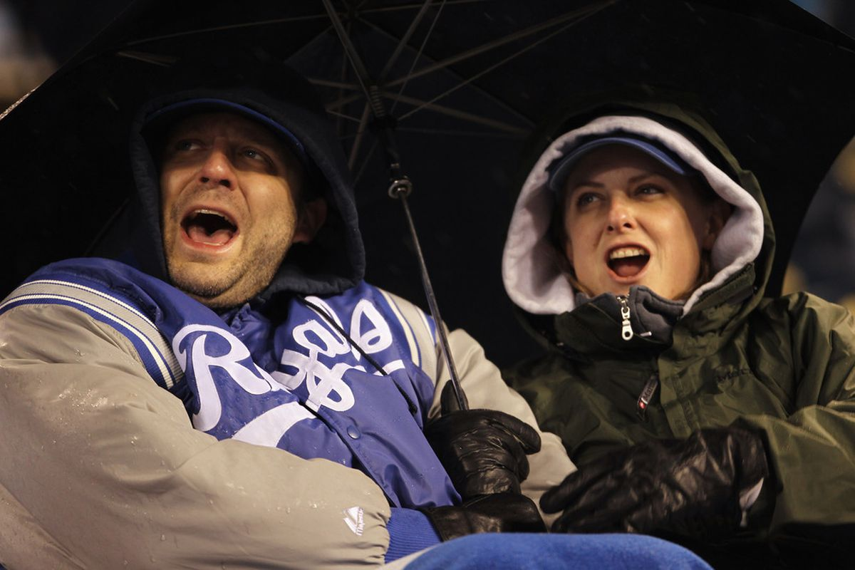 KANSAS CITY, MO - APRIL 15:  Fans cheer under an umbrella on a rainy night during the game between the Seattle Mariners and the Kansas City Royals at Kauffman Stadium on April 15, 2011 in Kansas City, Missouri.  (Photo by Jamie Squire/Getty Images)