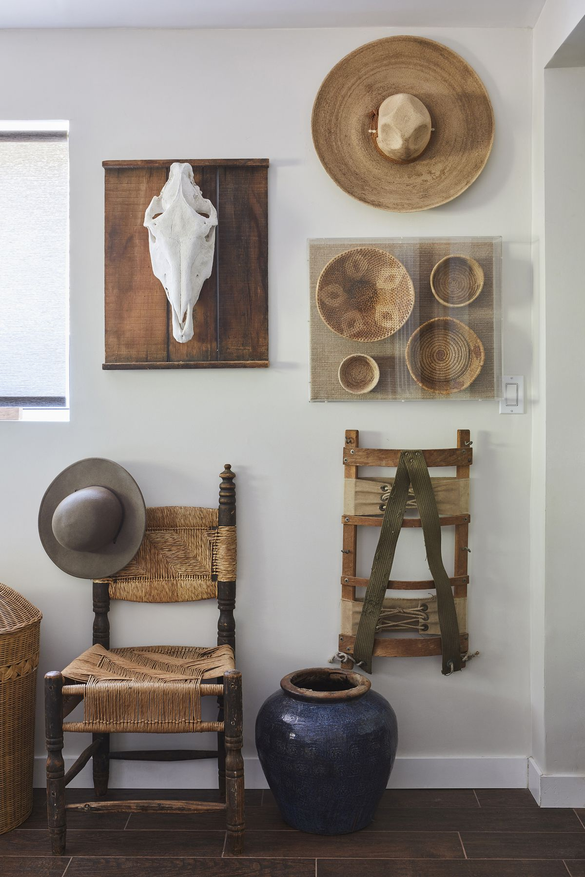 A wall has a straw hat, a white steer skull, a group of woven baskets, and a backpack rack hang on the wall over a wood-and-wicker chair.