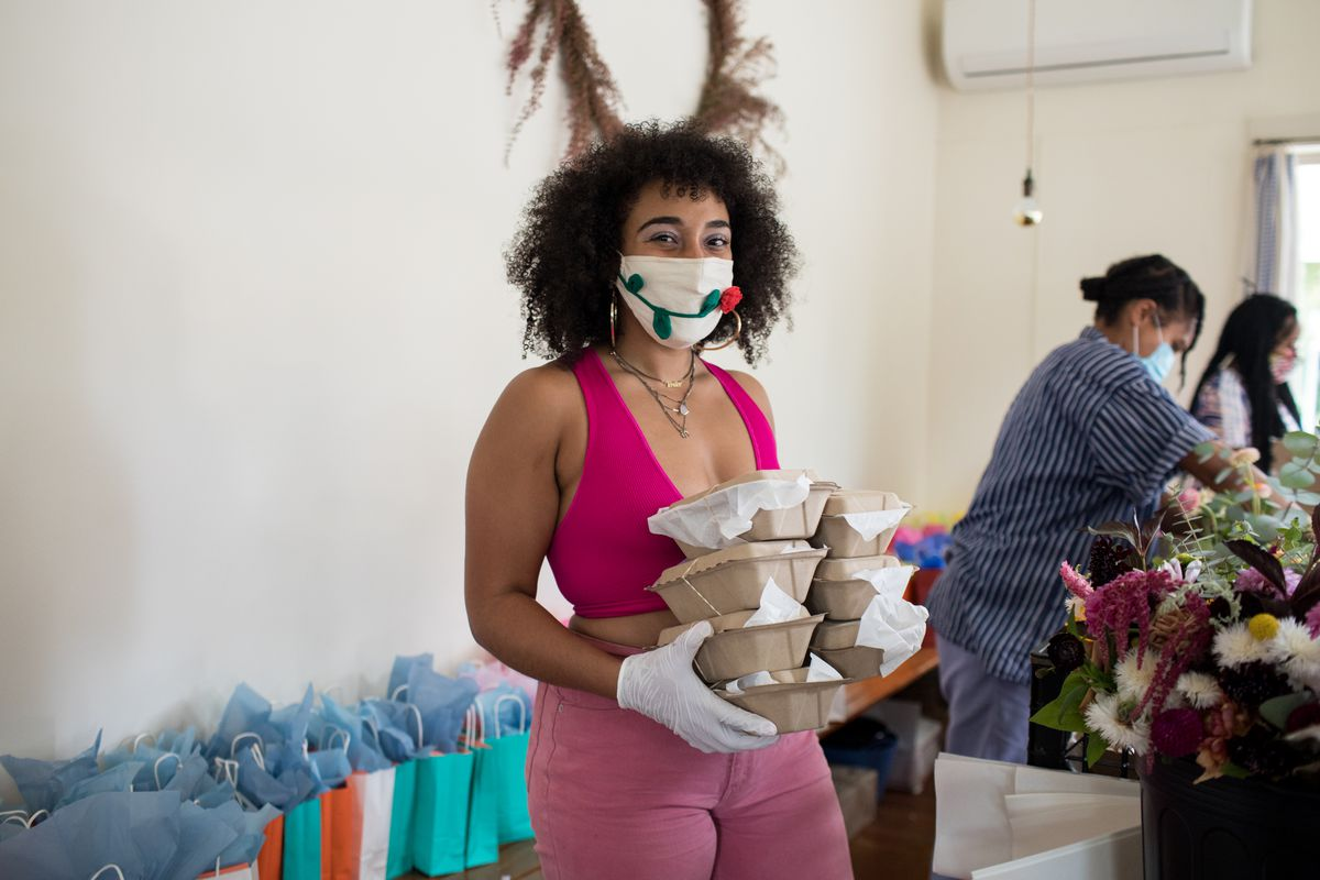 Woman wearing mask and gloves holds a stack of takeout containers.