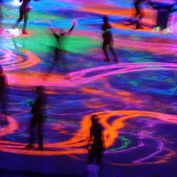 Skaters paint the ice with ultaviolet paint during the Salt Lake 2002 Winter Games closing ceremony at the University of Utah's Rice-Eccles Stadium on Sunday, Feb. 24, 2002.