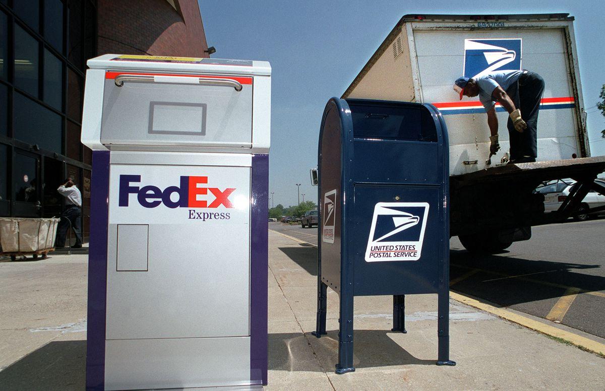 A FedEx box and a USPS box on a sidewalk beside a postal delivery truck.