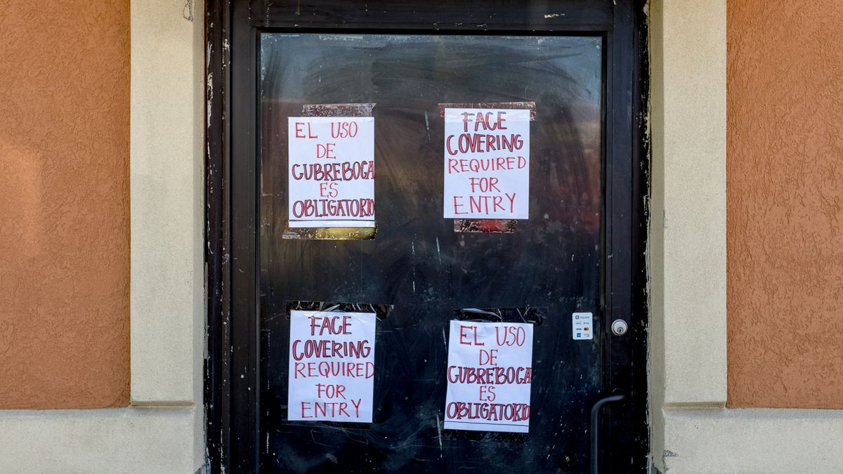 """Signs on a door say """"Face Coverings required for entry"""" in Spanish and English."""