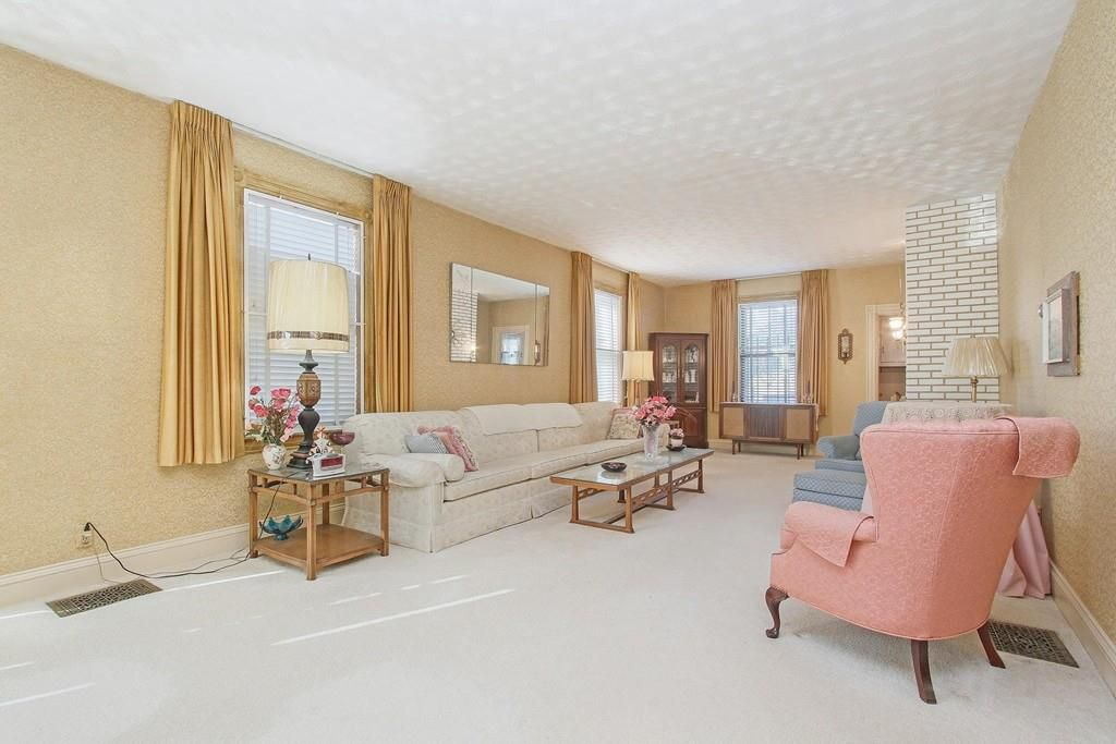 A long, plush living room with furniture and three windows.