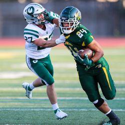 Kearns' Naki Leha (24) carries the ball against Olympus' Jordan Allred (27) during a high school football game at Kearns High School in Kearns on Friday, Aug. 28, 2020.