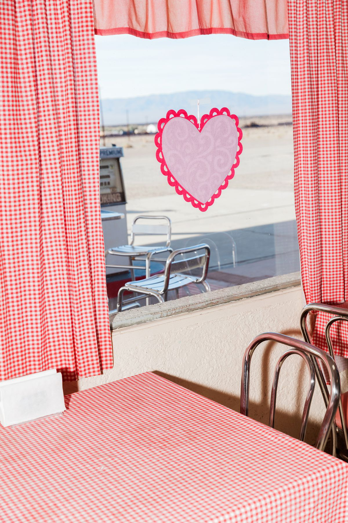 The interior of a diner. There is a table with a red and white checkered tablecloth and a chair. There are red and white checkered curtains. There is a paper heart on the window. The view outside is a desert.